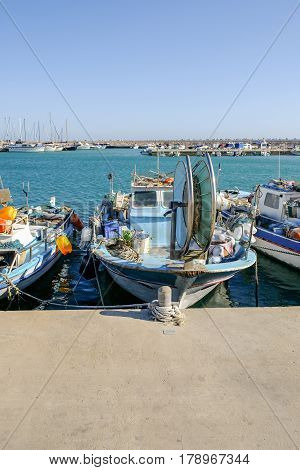 Fishing boat moored at Zygi, Cyprus, afternoon shot with blue sky.