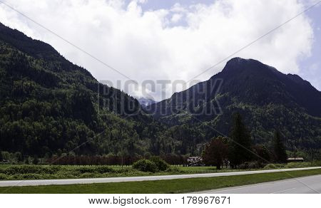 Wide view of the Rockies rising along the Trans Canada Highway with lush green trees, foliage and a house just outside of Hope British Columbia on a bright sunny day with blue skies and clouds in April.