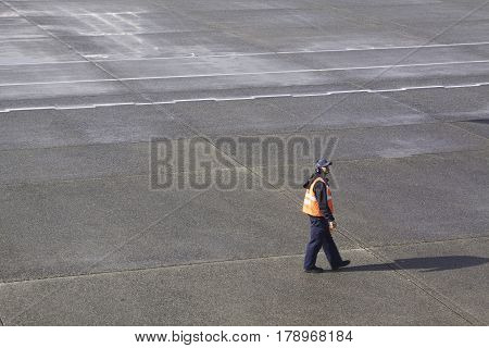 Montreal, Quebec - April 25, 2015 -- Wide view of a single airline worker walking on the tarmac of the Pierre Elliott Trudeau International Airport, Montreal, Quebec on a sunny day in April.