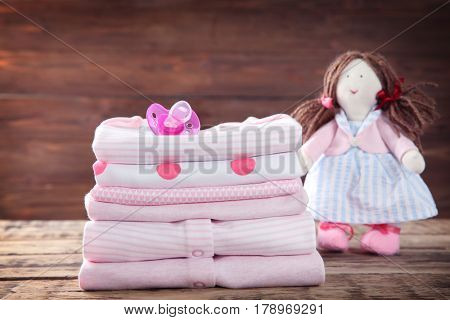 Pile of baby clothes on wooden background