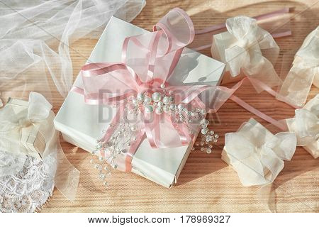 Beautiful gift boxes with bows and bridal veil on light background