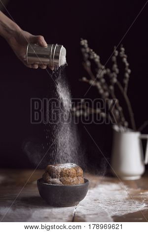 Detail of female hand sprinkling marble cake placed on a rustic wooden table with powdered sugar. Selective focus