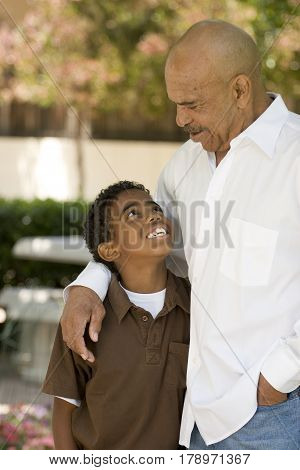 Happy African American grandfather and grandson smiling.