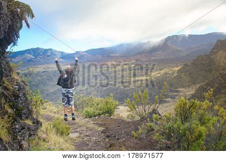 Happy boy with open arms standing in the mountains, feeling their immensity, embracing nature.