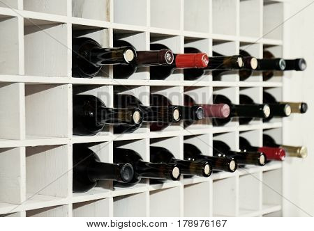Wine bottles on wooden racks in cellar