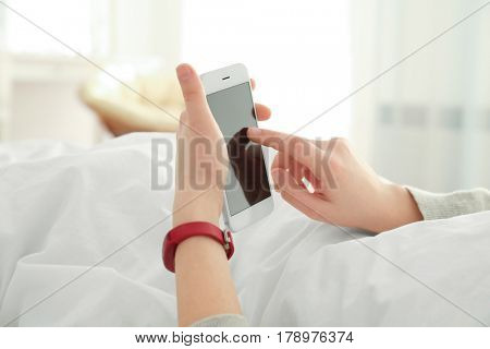 Young woman with sleep tracker and mobile phone lying in bed at home, closeup
