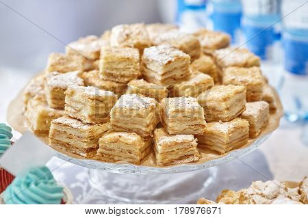 Stack of square bakery slices desserts or cakes on plate closeup