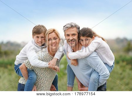 Parents giving piggyback ride to kids outside