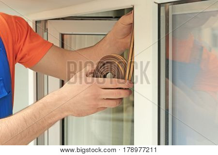 Hands of young worker applying rubber strip onto office window