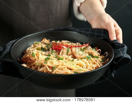 Woman holding frying pan with tasty chicken spaghetti, closeup
