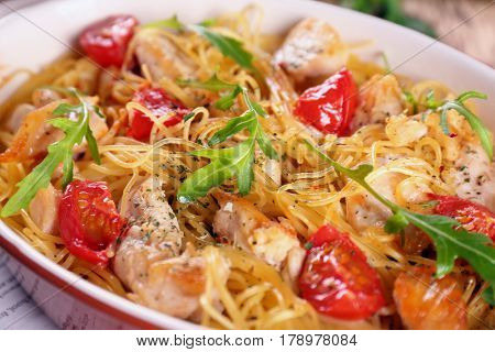 Delicious spaghetti with chicken, tomatoes and arugula in baking dish