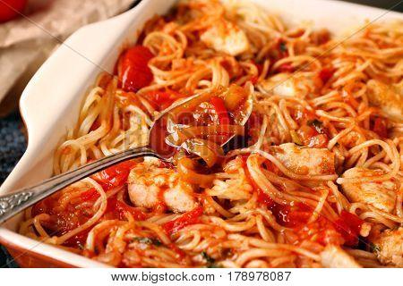 Delicious chicken spaghetti with tomato sauce in baking dish