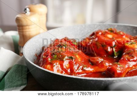 Frying pan with chicken cacciatore on table, closeup