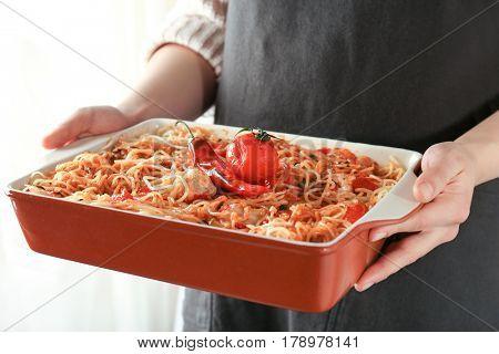 Woman holding baking dish with tasty chicken spaghetti, closeup