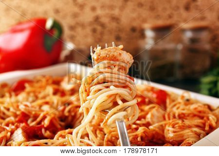 Fork with delicious chicken spaghetti and baking dish on background