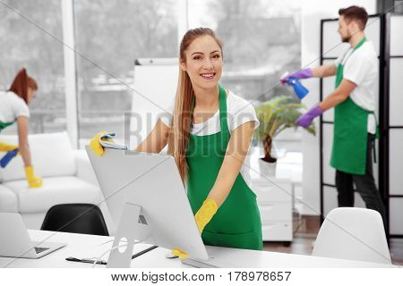 Young female cleaner wiping computer at office