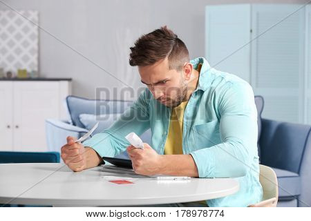 Shocked young man calculating taxes at home