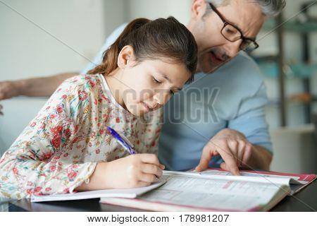 Man helping daughter with homework
