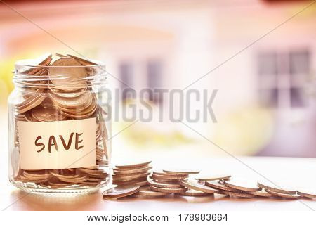 Coins in glass jar with house defocused background money saving for house or real estate loan concept