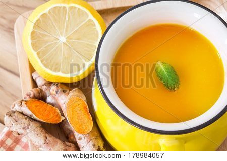 a cup of Turmeric Tea with lemon and ginger Benefits for reduce Inflammation Liver Detox and Cleanser healthy herb drink concept