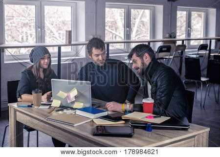 Young smart team. Group of modern people discussing project on meeting in the office. Working environment with laptop coffee notepads and stationery.