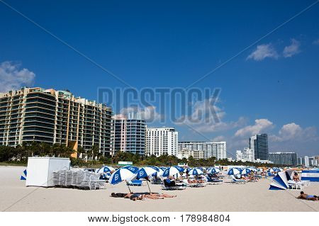 MIAMI BEACH FLORIDA - FEBRUARY 15 2017: Vacationers sunbath on Miami Beach Florida USA with hotels and condominiums in the background on February 15 2017.