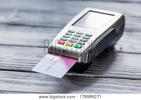purchase with payment terminal by credit card on woden desk background