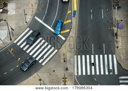 City street with crosswalks on asphalt road and car traffic. Fast city life transportation concept.