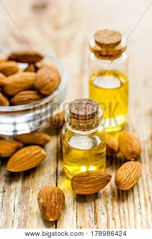 natural cosmetic and therapeutic almond oil for treatment on brown wooden table background