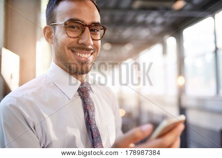 Portrait of a confident, happy business entrepreneur wearing fashionable tie and eyewear on his way to his next consultant meeting on the train platform