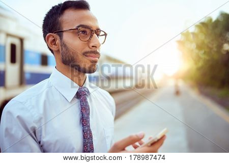 Confident serious millennial businessman on the go consulting his mobile phone in a train station at sunset