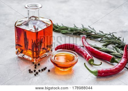 Glass bottle with bright chili oil and herbs on stone table background