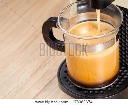 Single-serving coffee machine dispenses  espresso in a glass cup