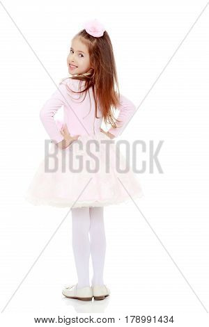 Dressy little girl long blonde hair, beautiful pink dress and a rose in her hair.She turned her back to the camera and looks over his shoulder.Isolated on white background.