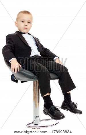 Beautiful little boy in a strict black suit , white shirt and tie.He sits in a spinning chair.Isolated on white background.