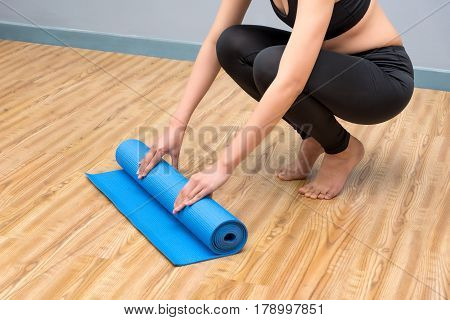 Young asian woman prepare her yoga mat at indoor yoga healthy sport gym. Yoga and meditation have good benefits for health. Photo concept for Yoga Sport and Healthy lifestyle.