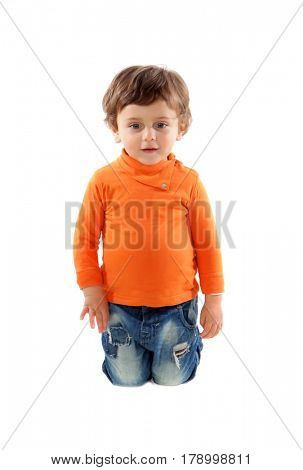 Playful baby on knees with orange jersey isolated on a white background