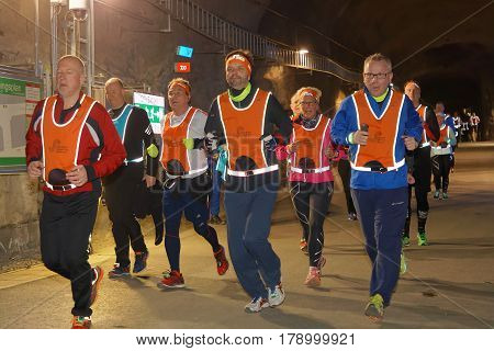 STOCKHOLM SWEDEN - MAR 25 2017: Closeup of many runners in reflex vest in a dark tunnel in the Stockholm Tunnel Run Citybanan 2017. March 25 2017 in Stockholm Sweden