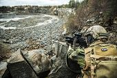 Norwegian Rapid reaction special forces FSK soldier in field uniforms in ambush among the rocks guarding perimeter waiting enemy poster