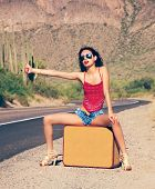 Beautiful young lady with case hitching a ride on a lonely hot desert road poster