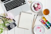Feminine flat lay workspace with watercolor paintbrushes laptop cup of tea photo camera and flowers on white wooden table. Top view mock up. poster