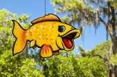 Hanging yellow fish mobile from a chain with trees and blue sky background poster