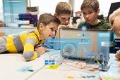 education, children, technology, science and people concept - group of happy kids with laptop computer and invention kit at robotics school lesson with virtual screen projection poster