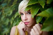 Portrait of an urban boyish blonde millennial girl looking cute, shy and being flirty in front of a leafy background. poster