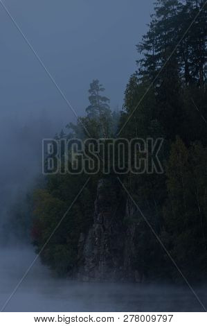 Riverbank At Dawn With Trees On Rocks Covered In Thick Fog