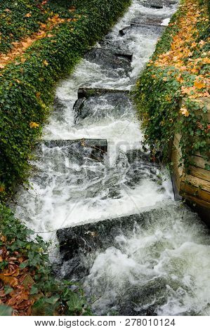 Small Cascading Stream With Colourful Autumn Leaves On Both Banks