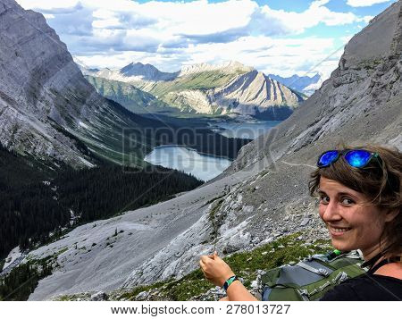 A Young Woman Hiker Admiring The View From The Side Of The Mountain.  Down Below Is The Rockies And