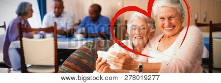 Heart against portrait of smiling senior woman taking selfie with friend