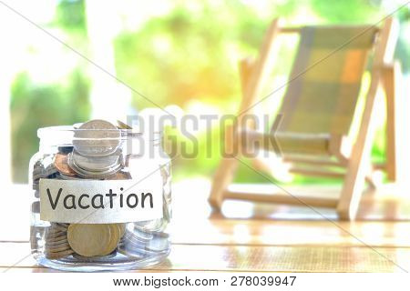 Vacation budget concept. Vacation money savings concept. Collecting money in moneybox for Vacation. Money jar with coins and beach chair poster