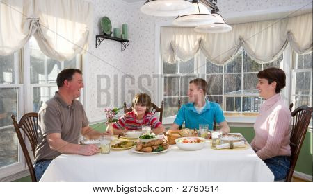 Happy Family Eating At Dinner Table